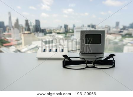 USB hub and modern minimal clock with men glasses on office desk