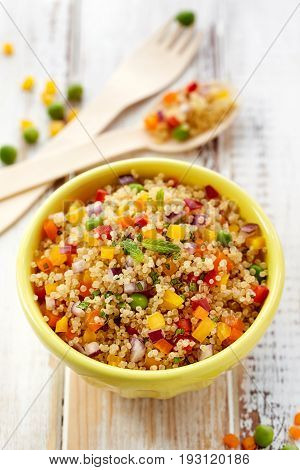 Quinoa salad with addition of pepper, red onion, green peas and fresh mint,  healthy and nutritious vegan dish