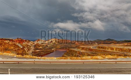Wide angle view of copper mine open pit in Rio Tinto with road, cloudy day, Spain