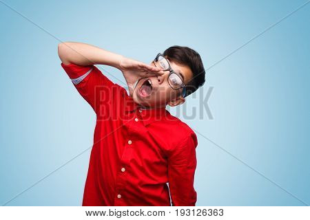 Kid in red shirt and glasses posing on blue background shouting loud with hand near mouth.