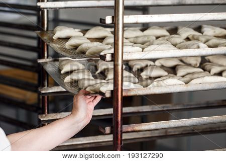 billet bun of dough with filling inside. Prepared for baking in baking production. manufacturing of food products. Baker lays out the workpiece, the hand closeup