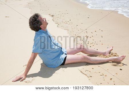 handsome smiling mature man sit on summer beach