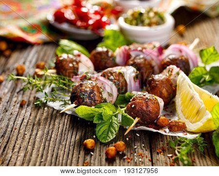 Kofta skewers, meatballs and red onion with addition of fresh mint and thyme, delicious  oriental cuisine
