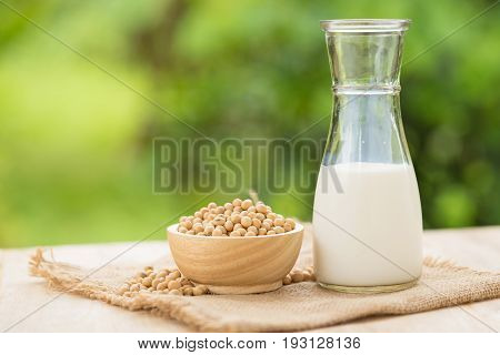 Soy Milk And Soy Beans In Wooden Cup With Abstract Blurred Forest Nature Background.