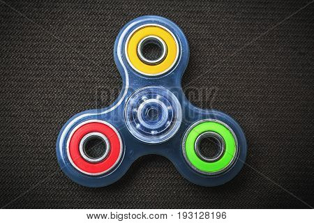 Blue transparent Fidget Spinner with colorful rings, stress relieving toy on black textured background, top view