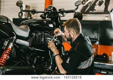 Professional mechanic working screwdriver and motorcycle repairs. Handsome young man repairing motorcycle in repair shop.