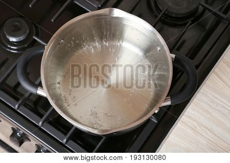 Water boiling into saucepan on the gas stove