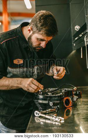 Motorcycle mechanic replacing glow plugs in bike engine. Spark plug replacement work in repair shop.