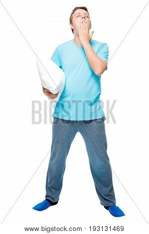 Yawning Sleepy Man With A Pillow In His Pajamas On A White Background In Full Length