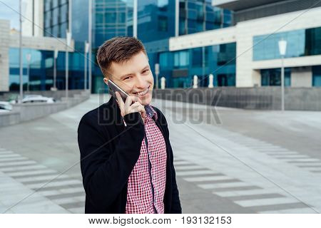 Happy young man in plaid shirt and jacket walking in the city and talking on cell phone outdoors. Student with mobile phone