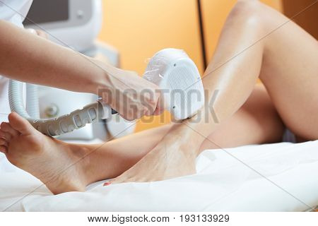 woman at cosmetics salon, legs laser epilation
