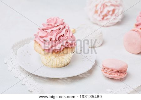Pink cupcakes with roses and macaroons. Festive and bright. Wedding Celebration concept