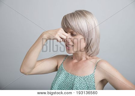 Female gesture smells bad. Portrait of woman wearing casually pinches nose with fingers hands looks with disgust something stinks bad smell situation. Human face expression body language reaction.