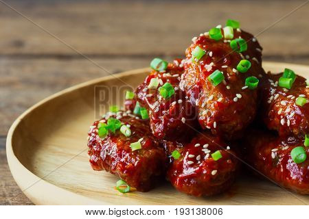 Korean fried chicken wings sprinkled with sesame and spring-onion on wood plate. Homemade Korean barbecue chicken wing delicious moist and spicy. Fried chicken wings in Korean style on wood table with copy space for background.