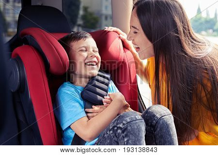 Mid shot of joyful mother tickling son sitting in baby seat