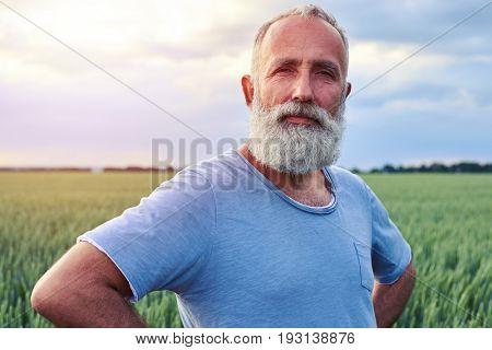 Close-up shot of senior grey bearded man holding hands on the waist and looking at the camera
