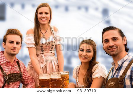 Waitress delivers beers in tent with happy visitors in a beer tent at Munich Oktoberfest against blurred blue background