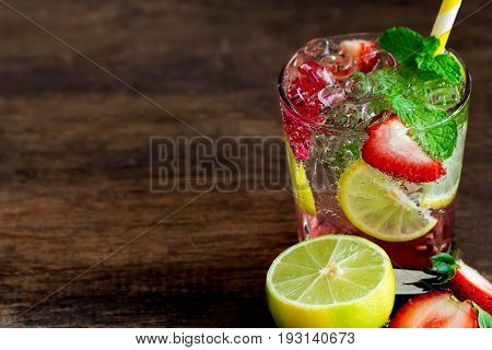 Strawberry lemon or lime soda in clear glass on rustic wood table. Homemade beverage strawberry soda ingredients with strawberry lemon or lime mint leaf and sparkling water. Close view of strawberry lemon soda on wood plank with copy space.