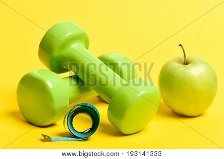 Apple In Yellow Near Green Dumbbells And Cyan Measuring Tape