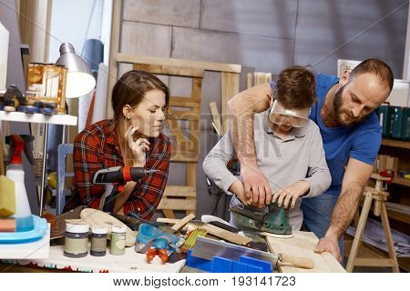 Diy father teaching son in workshop, mother watching.