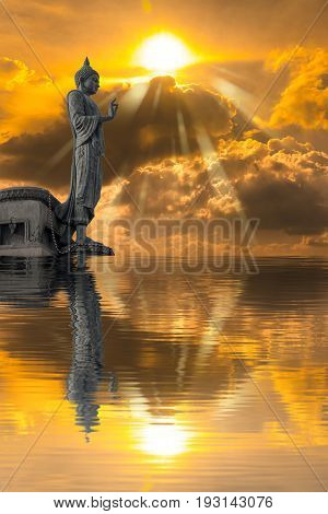 Buddha statue against on Golden sky with sunlight and water reflection. Abstract Religion.
