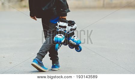 Toned baner llittle beautiful boy with roller skates in his hands. Street culture backgroung