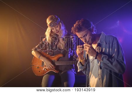Female guitarist performing with musician playing harmonica in nightclub