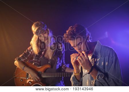 Female guitarist looking at male musician playing harmonica in music concert