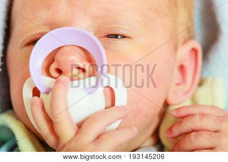 Infant care beauty of childhood concept. Little newborn baby lying calmly in bed with teat in mouth closeup.