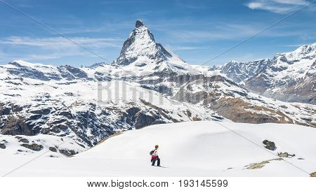 ZERMATT, SWITZERLAND - May 16. 2017: Hiker walking on snow towards Matterhorn Mountain with white snow and blue sky in Zermatt city in Switzerland
