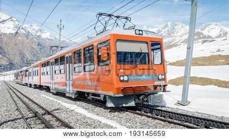 ZERMATT, SWITZERLAND - May 16. 2017: Red train climbing up to Gornergrat station on Zermatt, Switzerland. The Gornergrat rack railway is the highest open-air railway in Europe.