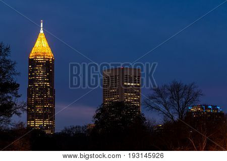 Night view of illuminated skyscrapers of Midtown and Downtown Atlanta through trees USA