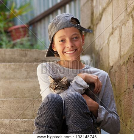 Happy teenager outdoors with kitten. Smiling boy