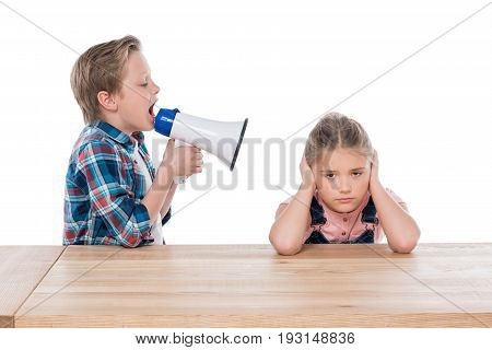 Angry Boy With Megaphone Yelling On His Sad Sister Isolated On White
