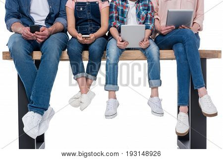 Low Section Of Family Using Different Digital Devices Isolated On White