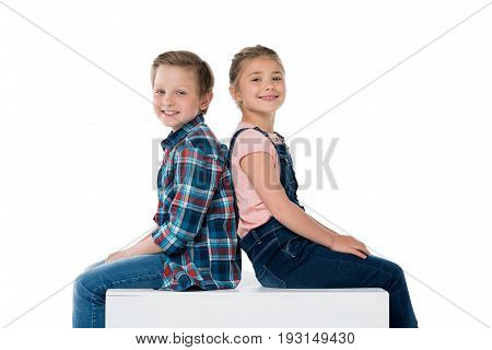 side view of smiling children sitting on cube and looking at camera isolated on white
