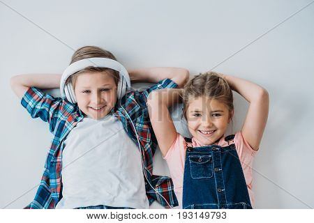 Adorable Pre-adolescent Kids Looking At Camera With Hands On Head
