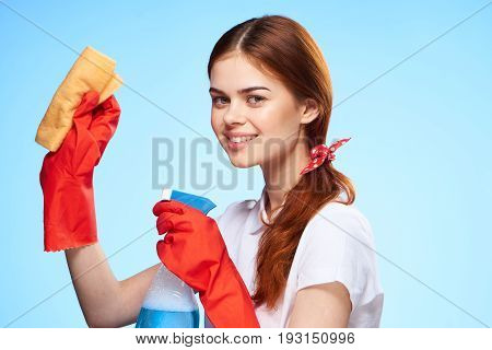 Young woman on a blue background, cleaning, rubber gloves, housework.