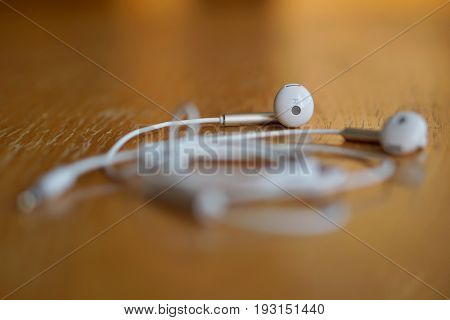 Macro detail of white modern earphones in futuristic design on the wooden background as a symbol of listening to music with the trendy equipment