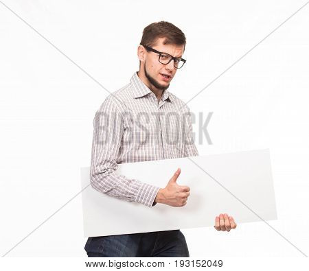 Young saxy man portrait of a confident businessman showing presentation, pointing paper placard gray background. Ideal for banners, registration forms, presentation, landings, presenting concept.
