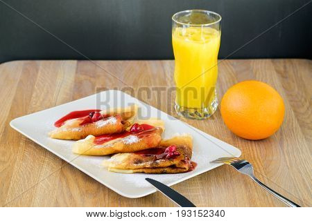 delicious breakfast of pancakes under syrup with juice