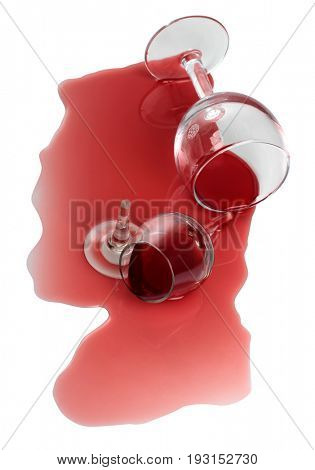 Broken glass and spilled red wine on white background
