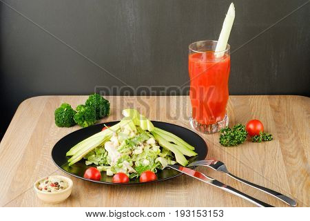salad served on a black plate with tomato juice