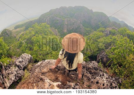 Happy female traveler with hat sitting on top of a mountain and enjoying viewpoint of Thailand.