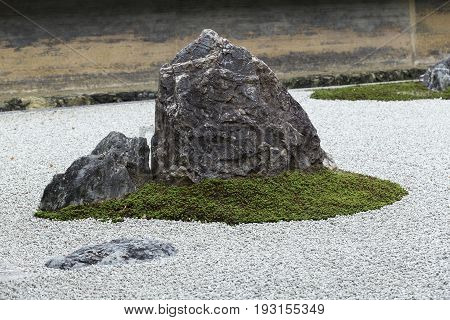 Zen Rock Garden in Ryoan-ji Temple.In a garden fifteen stones on white gravel Kyoto Japan