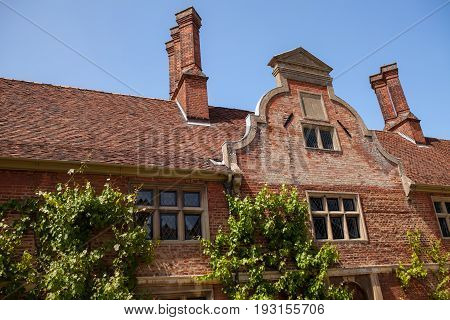 Dutch gable facade. Architectural detail on period red brick building with vintage leaded windows.