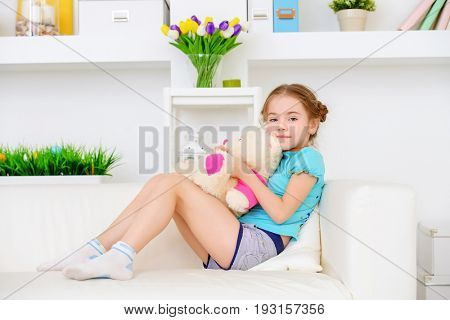 Happy girl playing with her teddy bear at home. Free time, activity and hobby. Family concept.