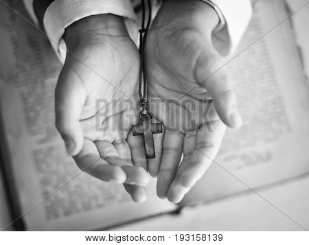 Church small cross in children's hands on the background of the Bible