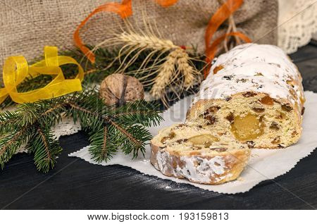 Christmas food card. Traditional Christmas stollen German festive dessert. Stollen cake cut. Black background.