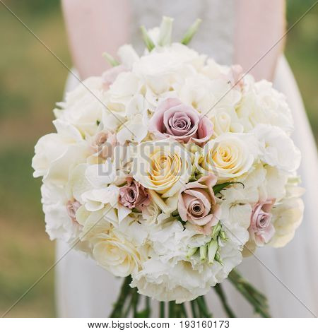 Bride in a dress standing in a green garden and holding a wedding bouquet of flowers and greenery. Woman holding colorful bouquet with her hands on wedding day.